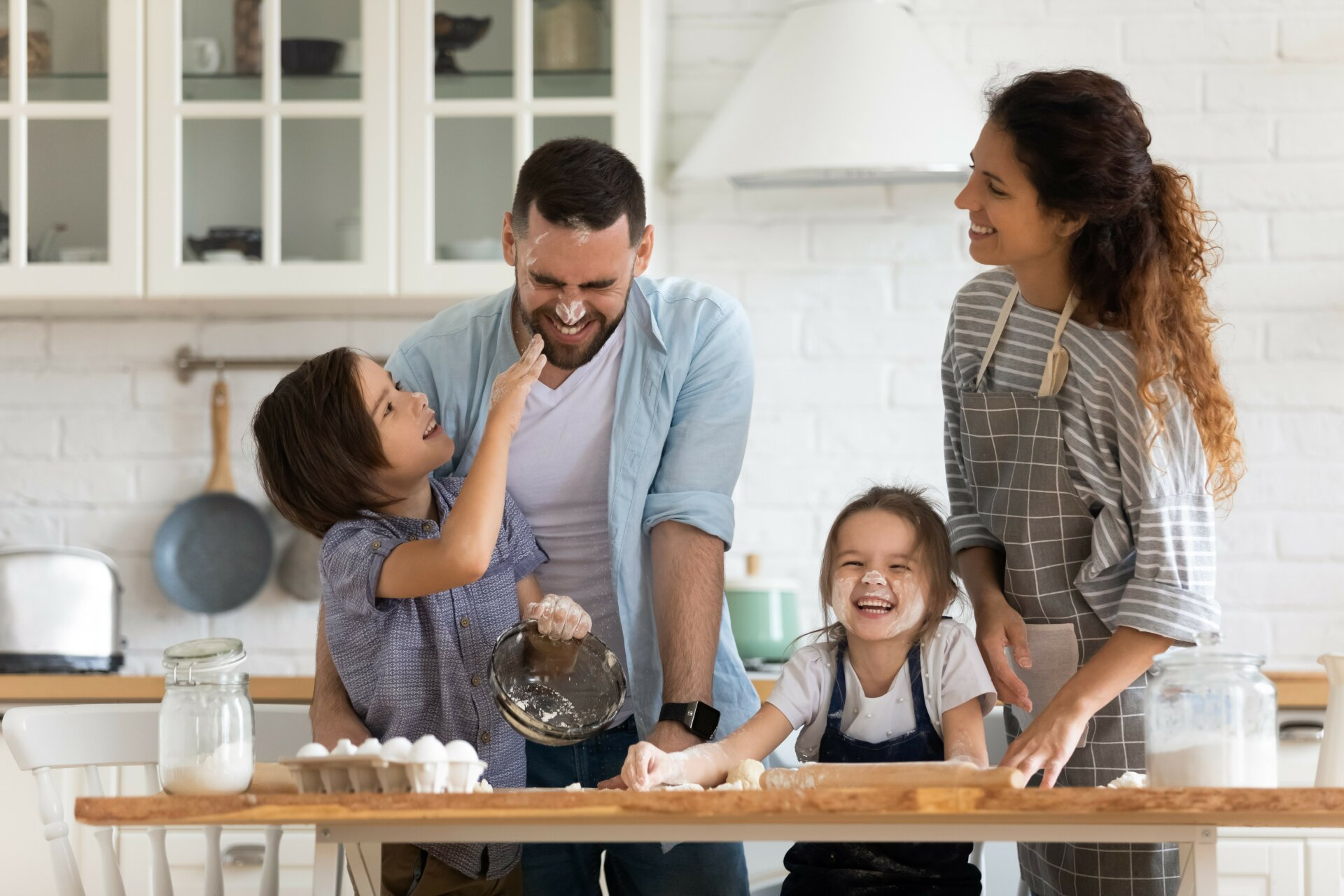 A father, mother, son and daughter bake playfully together in a beautiful, modern kitchen with stylish white cupboards in the background.