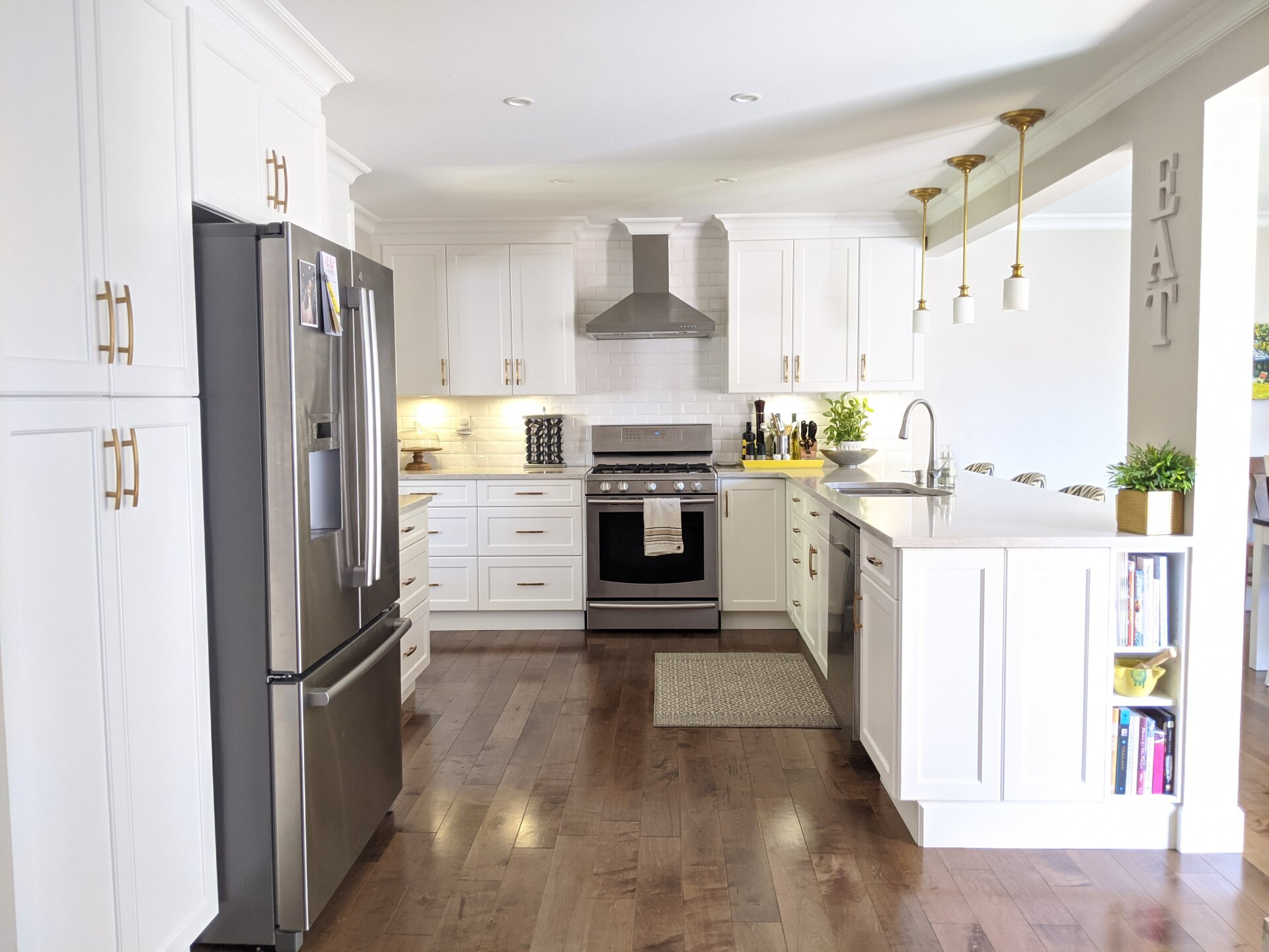 A recently renovated Vancouver kitchen with white, flat panel cabinets and gold hardware.