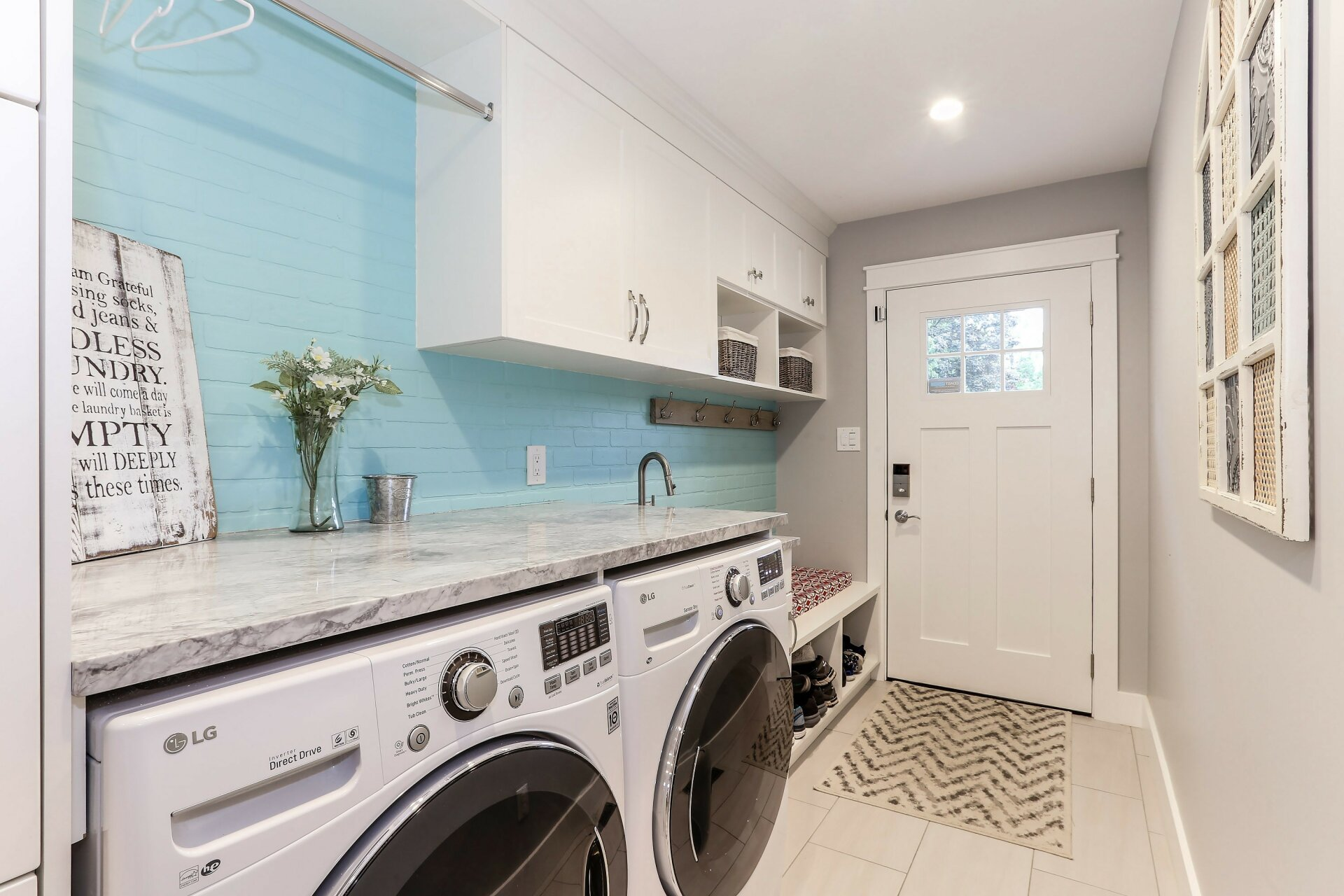 A Vancouver mudroom, with a washer-dryer, shoe storage bench seat and Shaker cupboards.