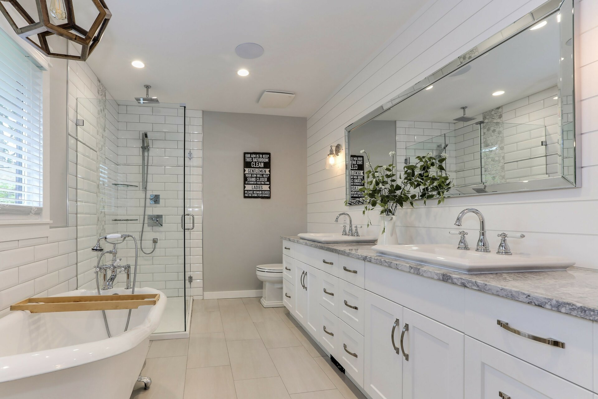 A beautiful renovated bathroom, featuring full bath, white vanities and his and hers sinks.